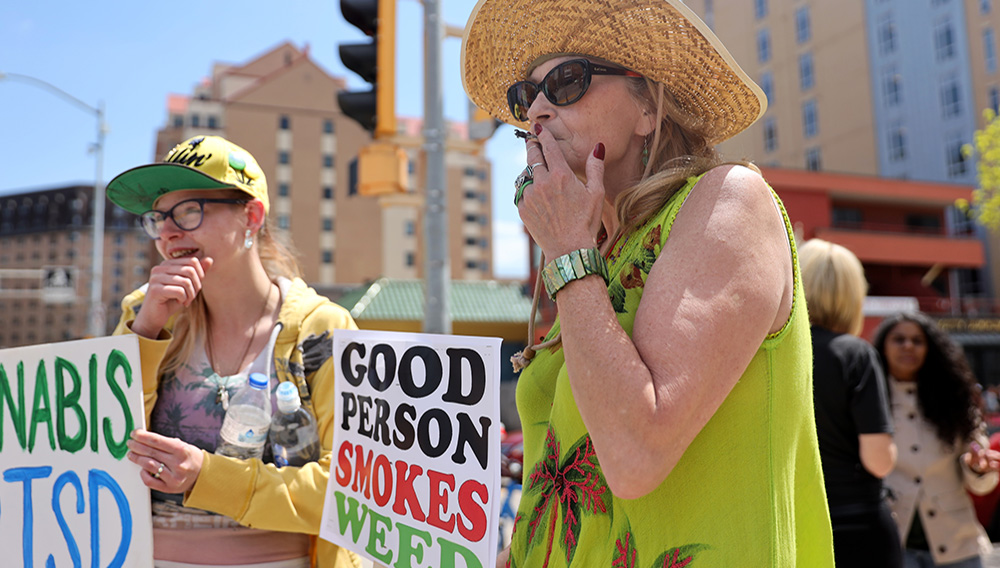 Liisa Kemp, 60, smokes a joint as supporters gather for a pro-marijuana legalization march in Madison, Wis., on May 4, 2019. | Emily Hamer/Wisconsin Center for Investigative Journalism