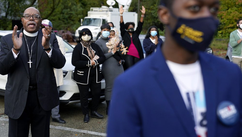"""Supporters listen to Democratic presidential candidate former Vice President Joe Biden speak at a """"Souls to the Polls"""" drive-in rally at Sharon Baptist Church, Sunday, Nov. 1, 2020, in Philadelphia. (AP Photo/Andrew Harnik)"""