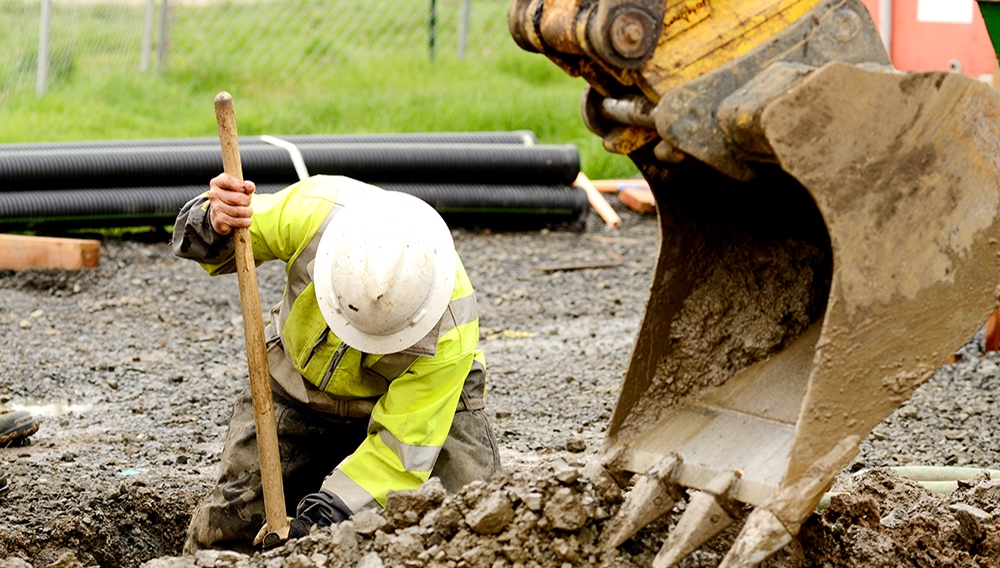 Worker using a small tracked excavator to dig a hole to fix a water leak at a large commercial housing development in Oregon. | Photo: iStock