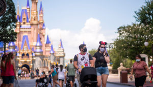 Guests wearing required face masks due to the COVID-19 pandemic stroll along Main Street, U.S.A. in front of Cinderella Castle at Walt Disney World Resort's Magic Kingdom on Wednesday, August 12, 2020, in Lake Buena Vista, Fla. (Photo by Charles Sykes, Invision/AP)