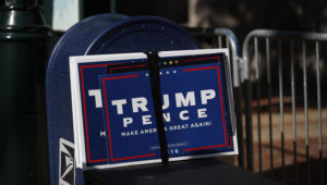Trump signs sit beside a mailbox as supporters of President Donald Trump set up to protest outside the Pennsylvania Convention Center, where vote counting continues, in Philadelphia, Monday, Nov. 9, 2020, two days after the 2020 election was called for Democrat Joe Biden. (AP Photo/Rebecca Blackwell)