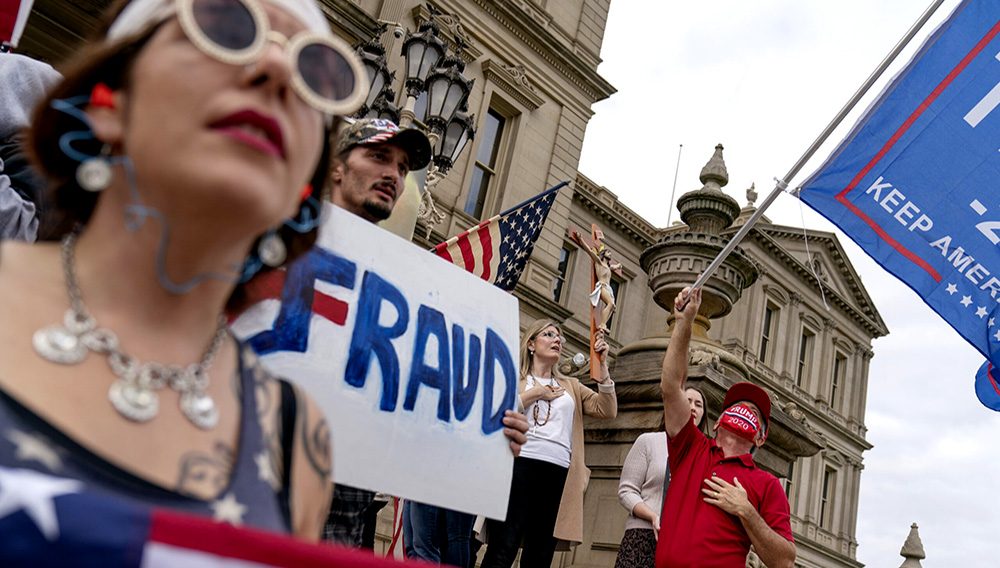 Trump supporters sing the National Anthem while protesting the presidential election results at the State Capitol in Lansing, Michigan, Sunday, Nov. 8, 2020. (AP Photo/David Goldman)