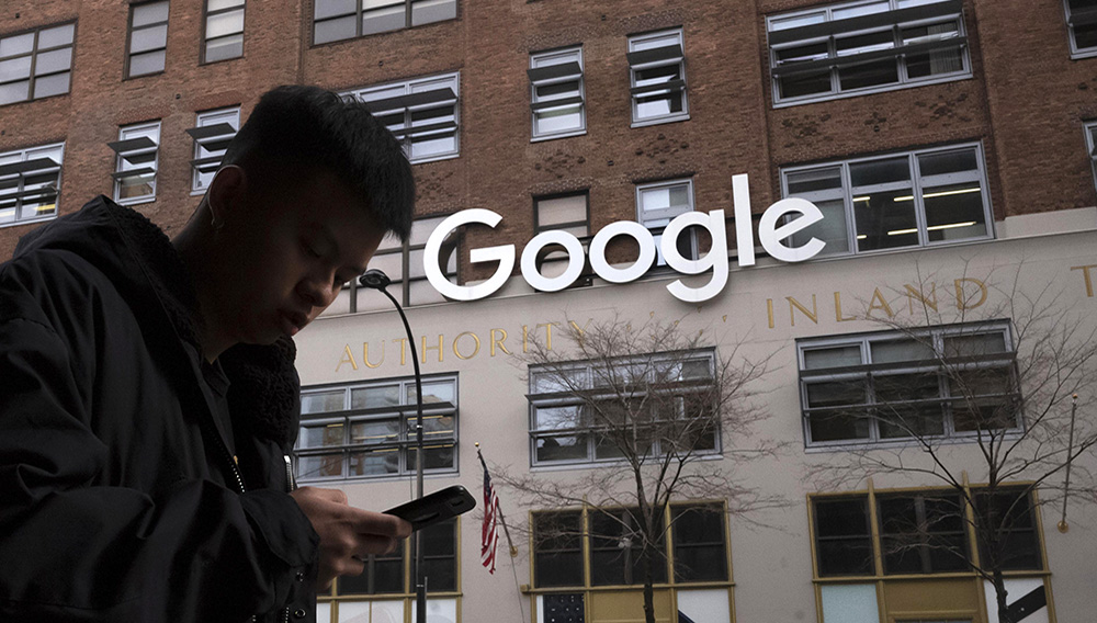 FILE - In this file photo dated Monday, Dec. 17, 2018, a man using a mobile phone walks past Google offices in New York. Monopoly or not, small business owners' biggest complaint about Google is that its advertising policies favor companies with big marketing budgets. (AP Photo/Mark Lennihan, File)