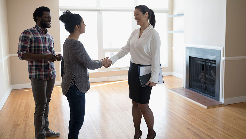 Young couple buying new house, handshaking with realtor in agreement. | Photo: iStock