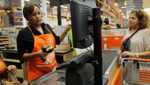 Barbara Chico (L) who was recently hired by The Home Depot rings up a sale for Rosanna Benhaddouch as she is trained on the cash register on February 16, 2012 in Miami, Florida. (Photo by Joe Raedle/Getty Images)