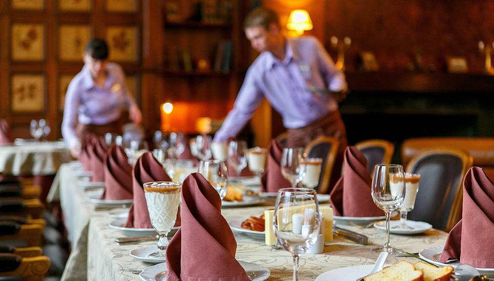 Waiters prepare a table for breakfast. Background. The foreground of napkins, dishes, toast, glasses. Calm atmosphere. | Photo: Ekaterina Oleshko/123RF.com