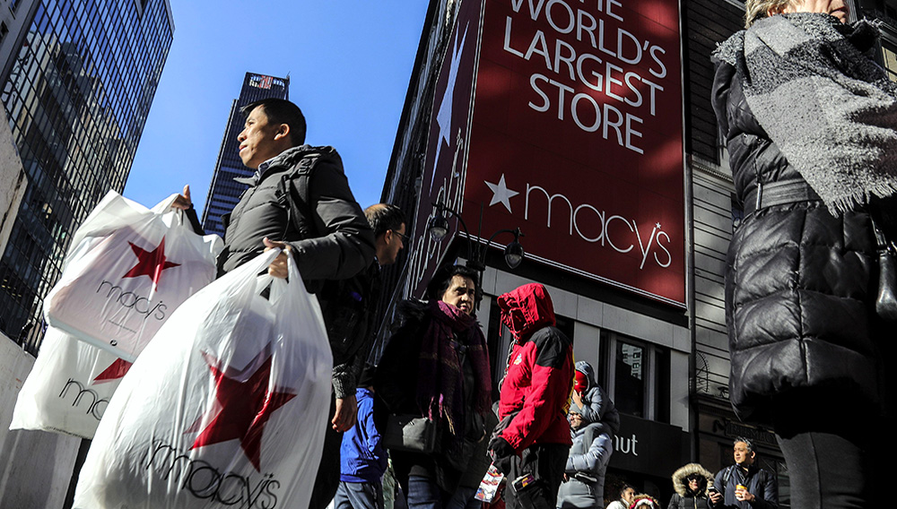 In this November 29, 2019, file photo a shopper leaves a Macy's department store with bags in both hands during Black Friday shopping in New York. (AP Photo/Bebeto Matthews, File)