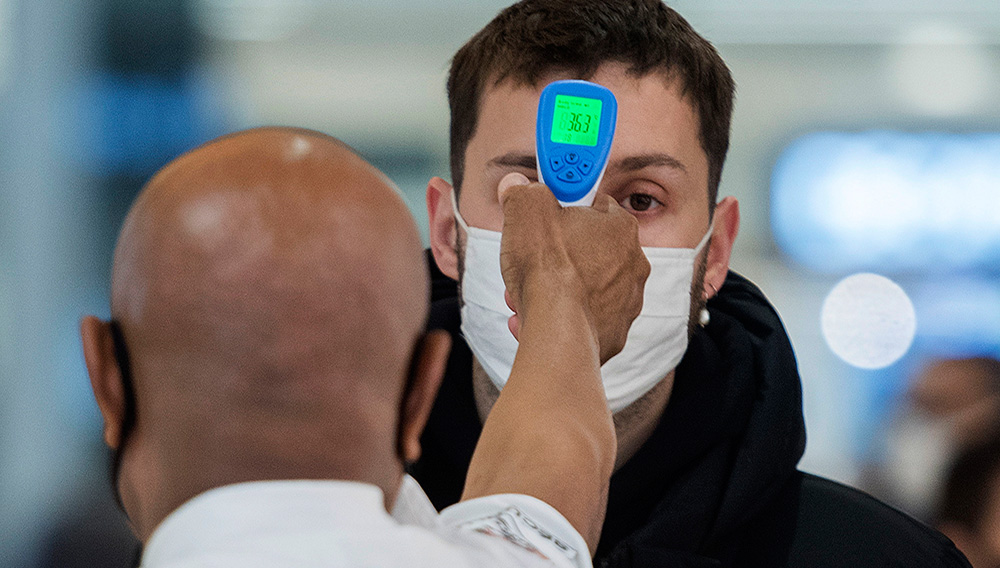 A man has his temperature checked prior to entering a store in Montreal, Sunday, November 22, 2020, as the COVID-19 pandemic continues in Canada and around the world. (Graham Hughes/The Canadian Press via AP)
