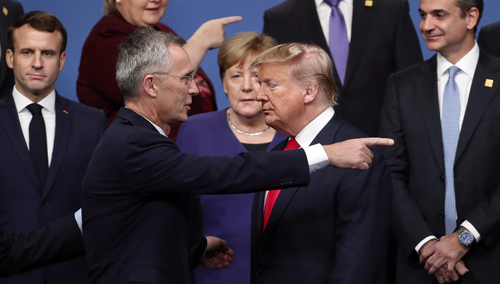 FILE - In this Dec. 4, 2019, file photo, NATO Secretary General Jens Stoltenberg, front left, speaks with U.S. President Donald Trump, front right, after a group photo at a NATO leaders meeting at The Grove hotel and resort in Watford, Hertfordshire, England. (AP Photo/Francisco Seco, File)