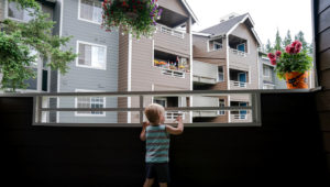 Grigory Vodolazov's 3-year-old son peers into his family's apartment complex from their unit in Bellevue, Washington. | Photo: Jovelle Tamayo for NPR