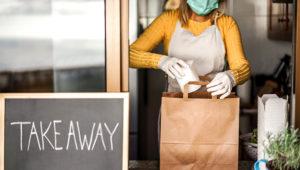 Young woman preparing takeaway healthy food inside restaurant during Coronavirus outbreak time. | Photo: DisobeyArt/istockphoto