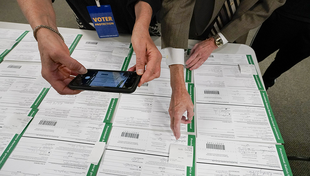 In this Nov. 6, 2020, photo, a canvas observer photographs Lehigh County provisional ballots as vote counting in the general election continues in Allentown, Pa. (AP Photo/Mary Altaffer, File)