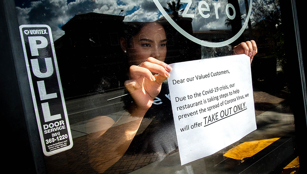 Supervisor Kryztel Natividad posts a notice on the door of Zero X, a coffee and tea cafe, in Riverside on Tuesday, March. 17, 2020, notifying customers of disrupted the service due to outbreak of novel coronavirus (COVID-19). (Photo by Watchara Phomicinda, The Press-Enterprise/SCNG)