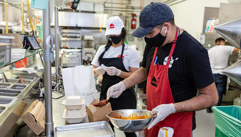 Eduardo Soto (right), kitchen manager, and Bua Vanitsthian, owner of Chicken as Cluck, pack an order for pickup on Wednesday, May 20, 2020, in San Francisco, California. | Photo: Constanza Hevia H.