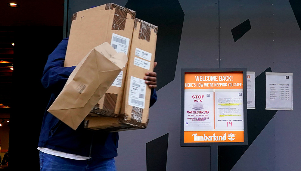 A shopper Wednesday, November 18, 2020, departs the Timberland Store near the store's COVID-19 safety requirements on Michigan Avenue in Chicago. (AP Photo/Charles Rex Arbogast)