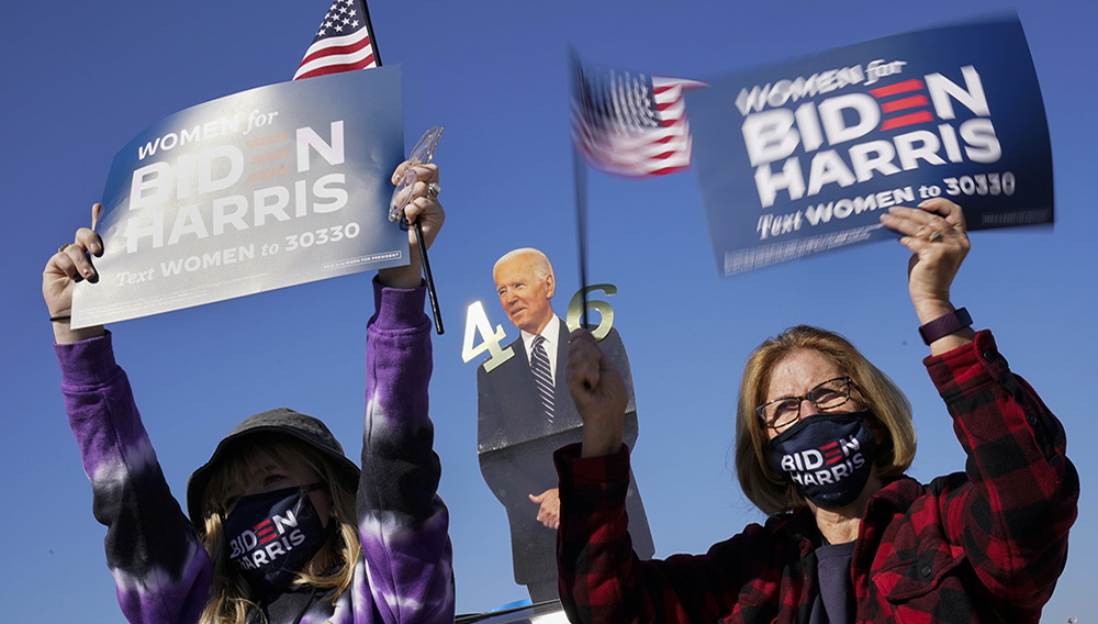 Supporters listen as Democratic presidential candidate former Vice President Joe Biden speaks at a rally at the Iowa State Fairgrounds in Des Moines, Iowa, Friday, Oct. 30, 2020. (AP Photo/Andrew Harnik)