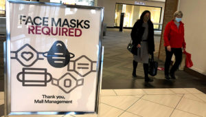 "In this November 13, 2020, file photo, a ""Face masks required"" sign is displayed at a shopping center in Schaumburg, Illinois. (AP Photo/Nam Y. Huh, File)"