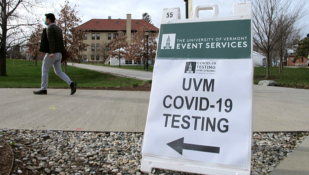 In this Nov. 12, 2020, photo, a University of Vermont student walks toward a tent leading to a COVID-testing site on campus in Burlington, Vt. As coronavirus cases are surging around the U.S., some colleges and universities are rethinking some of their plans for next semester. (AP Photo/Lisa Rathke)