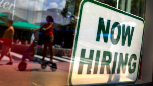 """A """"Now Hiring"""" sign is seen in the store front window on July 5, 2012 in Miami Beach, Florida. (Photo by Joe Raedle/Getty Images)"""