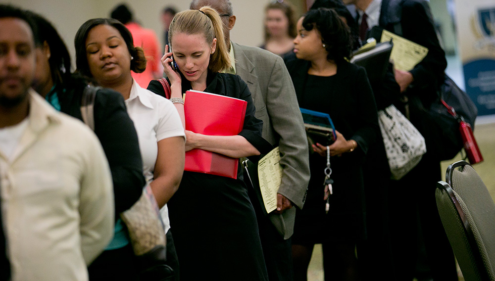 Job seekers wait in a line at a career fair in Arlington, Va. PHOTOGRAPH BY ANDREW HARRER — BLOOMBERG/GETTY IMAGES