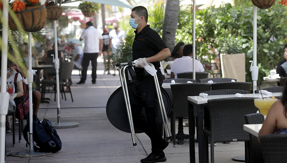 FILE - In this July 12, 2020, file photo, a waiter wears a protective face mask and gloves while working at the il bolognese restaurant along Ocean Drive during the coronavirus pandemic, in Miami Beach, Fla. (AP Photo/Lynne Sladky, File)