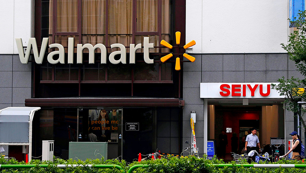 Company signs of Walmart and Seiyu are seen in Tokyo on July 12, 2018. U.S. retailer Walmart is selling off 85% of its wholly owned Japanese supermarket subsidiary Seiyu, while retaining a 15% stake, in a deal valued at ¥172.5 billion ($1.6 billion), the companies said Monday, Nov. 16, 2020. (Kyodo News via AP)
