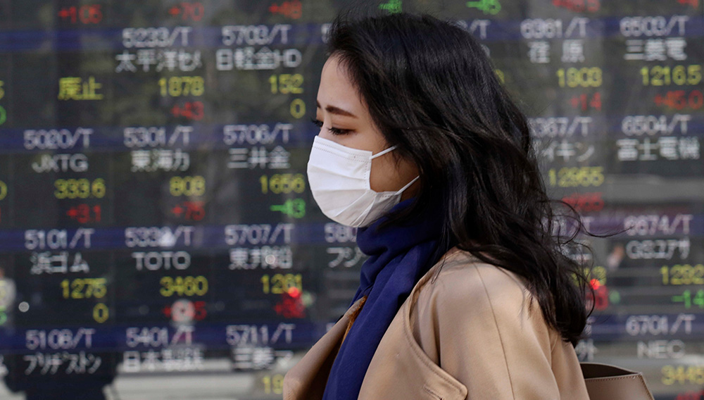 A woman walks by an electronic stock board of a securities firm in Tokyo, Wednesday, March 18, 2020. | Photo: Koji Sasahara/AP/Shutterstock