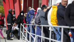 In this March 17, 2020, file photo, people wait in line for help with unemployment benefits at the One-Stop Career Center in Las Vegas. Americans who struggled through 2020 could face more hardship in the year ahead as pandemic related payments and protections come to an end. (AP Photo/John Locher, File)