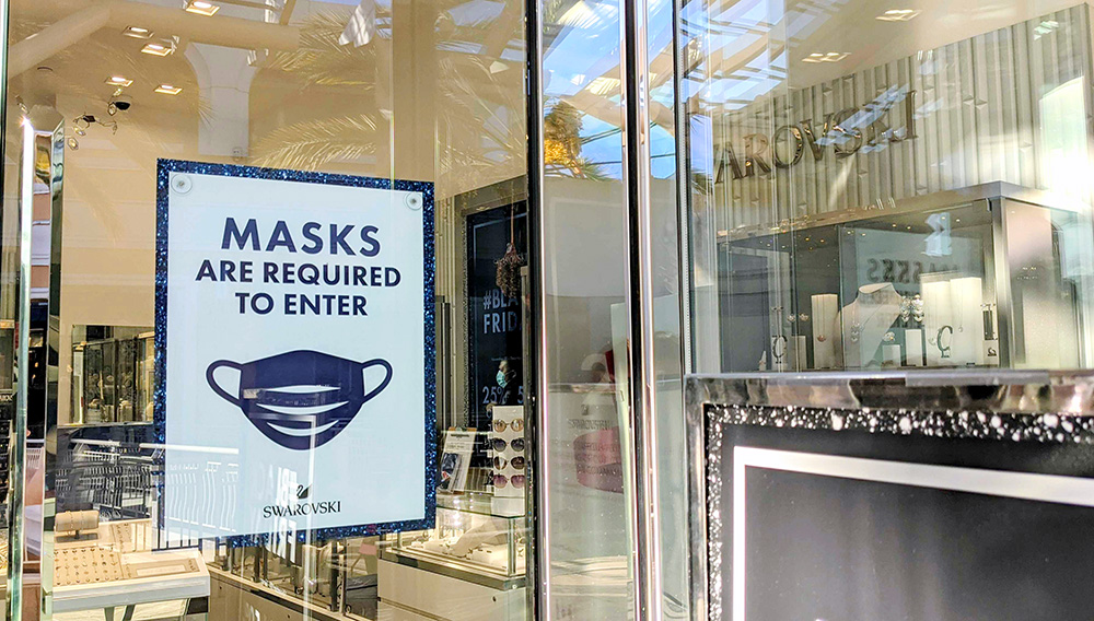 Above: A sign at the Swarovski store in Fashion Valley Mall asking shoppers to don a mask before entering in this file photo taken Nov. 28, 2020. | PHOTO BY ALEXANDER NGUYEN