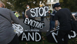 Housing activists erect a sign in front of Massachusetts Gov. Charlie Baker's house, Wednesday, Oct. 14, 2020, in Swampscott, Mass. Renters are still being evicted during the coronavirus pandemic despite a federal order that is supposed to keep them in their homes. (AP Photo/Michael Dwyer, file)