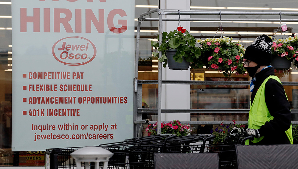 A man pushes carts as a hiring sign shows at a Jewel Osco grocery store in Deerfield, Ill., Thursday, April 23, 2020. Friday, Dec. 4, monthly U.S. jobs report will help answer a key question hanging over the economy: Just how much damage is being caused by the resurgent coronavirus, the resulting restrictions on businesses and the reluctance of consumers to shop, travel and dine out? (AP Photo/Nam Y. Huh)