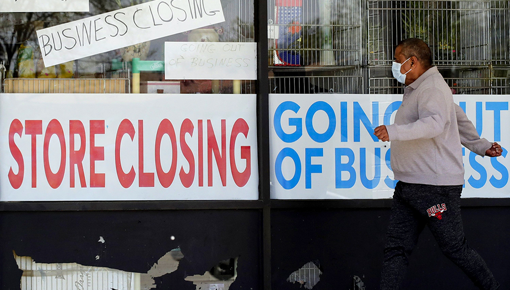 A man looks at signs of a closed store due to COVID-19 in Niles, Ill., May 21, 2020. | Associated Press