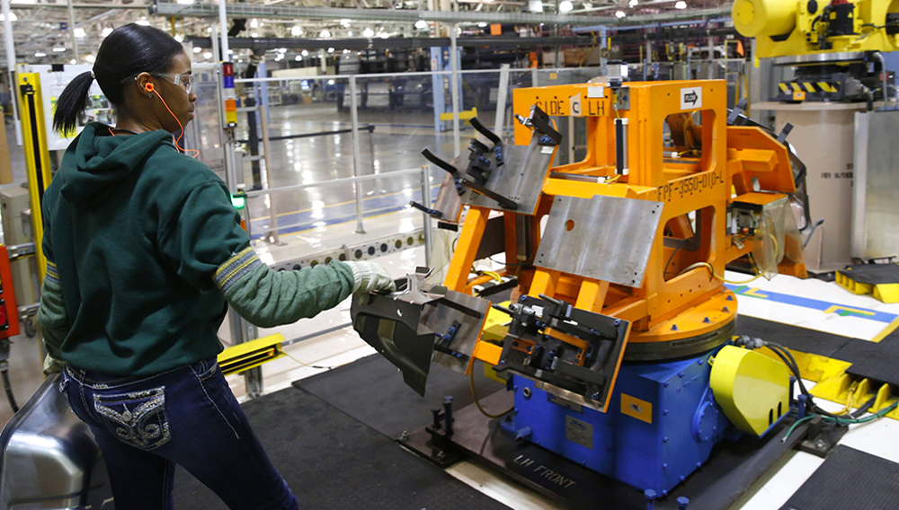Auto worker Imani Long assembles parts that will be welded by a robot for the Dodge Dart rear wheel house at Fiat Chrysler Automobiles NV's Warren Stamping Plant in Warren, Michigan, U.S., on Friday, Jan. 22, 2016. | Photo: Jeff Kowalsky/Bloomberg Finance LP