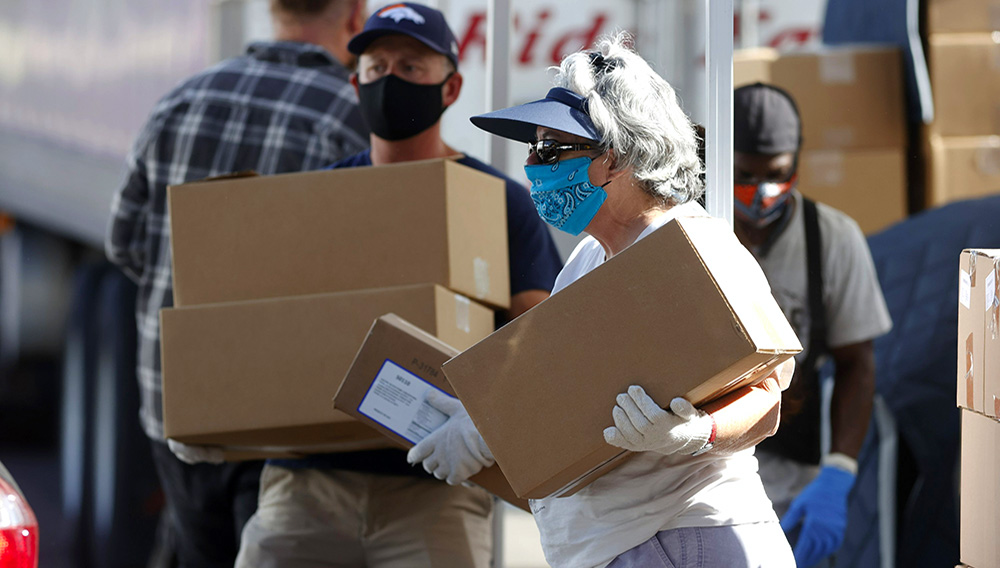 In this June 26, 2020, file photo, volunteers Juanita MacKenzie, front, and Dave Stutman carry boxes of food to a waiting car at a large mobile pantry set up by the Food Bank of the Rockies in the parking lot of Empower Field at Mile High in west Denver. (AP Photo/David Zalubowski, File)