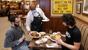 In this Sept. 30, 2020 file photo, waiter Lenworth Thompson serves lunch to David Zennario, left, and Alex Ecklin at Junior's Restaurant in New York. The U.S. services sector, where most Americans work, registered its fifth consecutive month of expansion in October 2020. (AP Photo/Mark Lennihan, File)