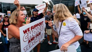 """People on both sides of the mask mandate in schools issue in Cobb County, Ga., face off Thursday ahead of a school board meeting in Marietta, Ga. Similar confrontations are happening across the country over masks and vaccines. """"The heat definitely got turned up this week,"""" said Shannon Portillo, a county commissioner in Kansas who was berated Wednesday at a meeting on masks. """"It got much more hostile than anything I had seen."""" (AP/Atlanta Journal-Constitution/Ben Gray)"""