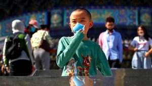 A child holds his protective face mask to help curb the spread of the new coronavirus as he visits to the capital's popular tourist spot of Temple of Heaven in Beijing, Sunday, May 10, 2020. (AP Photo/Andy Wong)