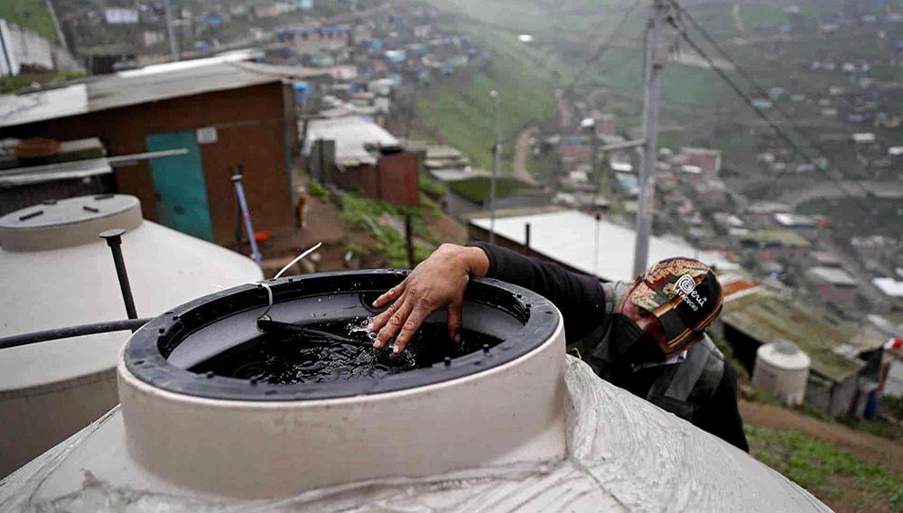 """Un hombre coloca su mano sobre el agua obtenida por los atrapanieblas colocados en el """"Muro de la vergüenza"""", en el asentamiento humano Pamplona Alta, el 04 de agosto de 2021 en Lima (Perú). EFE/Paolo Aguilar"""