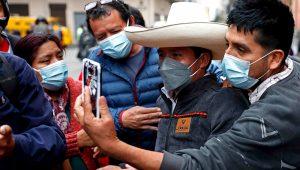 Samuel Carrillo, el doble del presidente del Perú —Pedro Castillo—, fue registrado al tomarse una foto con un transeúnte, en una calles de Lima (Perú). EFE/Paolo Aguilar