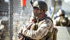 En esta imagen suministrada por el Cuerpo de Infantería de Marina de EEUU, un efectivo carga a un bebé durante las operaciones de evacuación en el Aeropuerto Internacional Hamid Karzai en Kabul, Afganistán, el jueves 26 de agosto de 2021. (Sgt. Samuel Ruiz/U.S. Marine Corps vía AP)