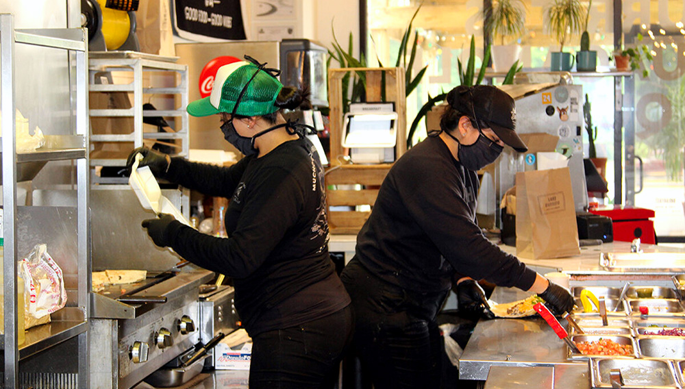 Dos mujeres preparan los pedidos de unos clientes en su restaurante Lake Burrito en Cumming, en el noreste de Georgia. EFE/Marcelo Wheelock/Archivo