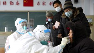 In this photo released by China's Xinhua News Agency, workers in protective suits take a swab for a coronavirus test in Shenyang in northeastern China's Liaoning Province, Monday, Jan. 11, 2021. (Yao Jianfeng/Xinhua via AP)