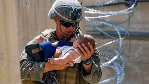 In this Aug. 21, 2021, photo provided by the U.S. Marine Corps, a U.S. Marine assigned to 24th Marine Expeditionary Unit (MEU) comforts an infant while they wait for the mother during an evacuation at Hamid Karzai International Airport in Kabul, Afghanistan. (Lance Cpl. Nicholas Guevara/U.S. Marine Corps via AP)