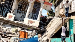 Residents survey a damaged building following a 7.2-magnitude earthquake in Les Cayes, Haiti, on Aug. 15. Photographer: Jonathan Alpeyrie/Bloomberg