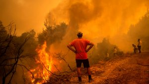 A volunteer watches as firefighters battle a forest fire in the Greek village of Glatsona on the island of Evia © Angelos Tzortzinis/AFP/Getty
