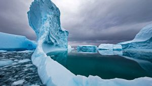 An iceberg melts in the waters off Antarctica. Climate change has accelerated the rate of ice loss across the continent. PHOTOGRAPH BY PAUL NICKLEN, NAT GEO IMAGE COLLECTION