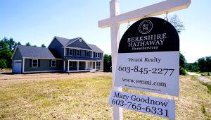 La foto de archivo del 24 de junio de 2021 muestra un cartel de inmobiliaria frente a una casa unifamiliar a estrenar en Auburn, Nuevo Hampshire. (AP Foto/Charles Krupa, File)