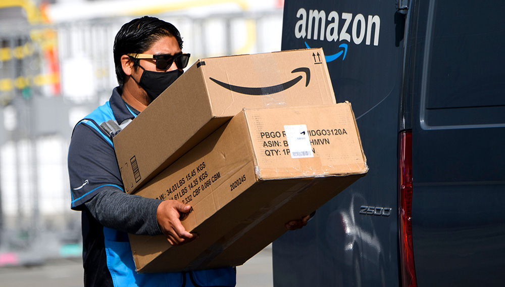 An Amazon.com Inc. delivery driver carries boxes into a van outside of a distribution facility on February 2, 2021 in Hawthorne, California. (Photo by PATRICK T. FALLON/AFP via Getty Images)