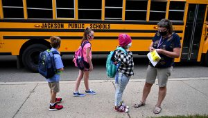 PHOTO: Students are given bus stickers after getting off the bus at Northeast Elementary School in Jackson on Tuesday morning, Aug. 25, 2020. | J. Scott Park | MLive.com