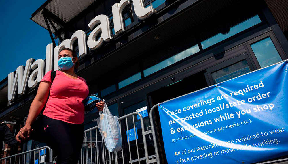 A woman wearing a face mask walks past a sign informing customers that face coverings are required in front of a Walmart store in Washington, DC on July 15, 2020. | Andrew Caballero-Reynolds | AFP | Getty Images